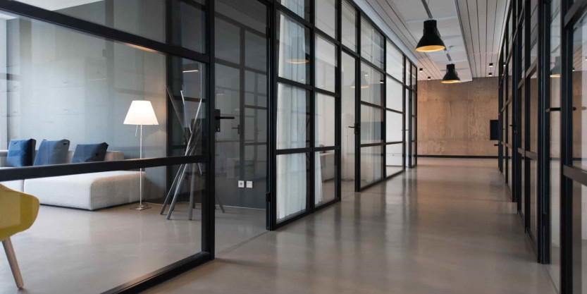 Hallway in commercial office space with glass windows showing modern meeting spaces